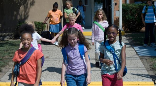 Children walking out of school building.