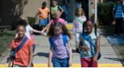Children walking out of school building.